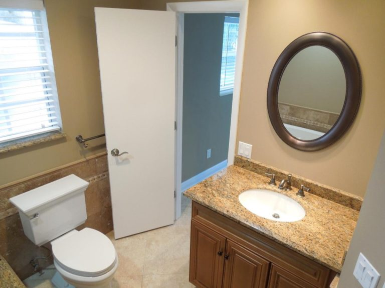 a newly renovated bathroom with new painted wall and granite tabletop sink