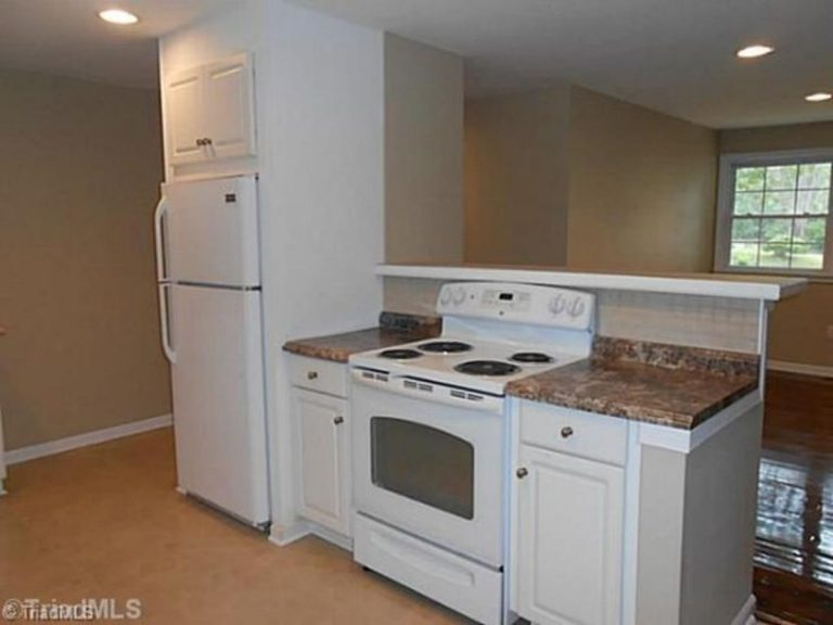 Refrigerator installed in the wall with electric oven in between the kitchen cabinet