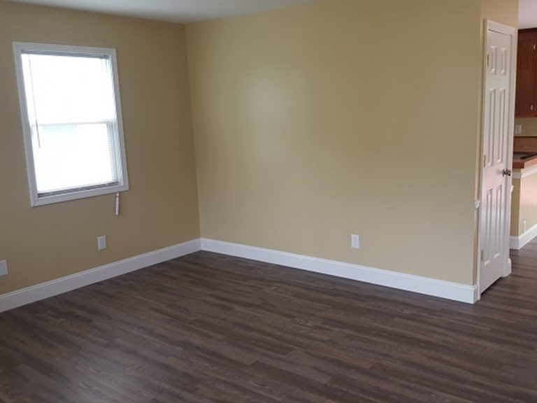 A newly painted wall and new flooring in a living room