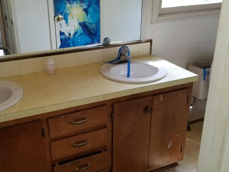 An old bathroom sink with wooden cabinet