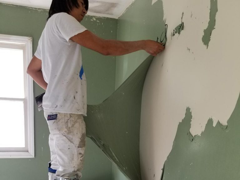 A contractor is removing the green paint on the wall