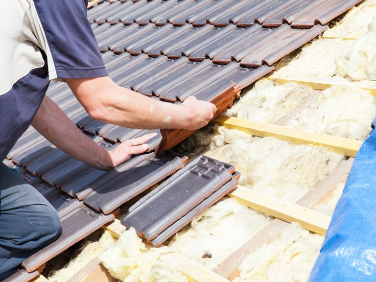 a Triad roofing contractor installing asphalt shingles on the rooftop