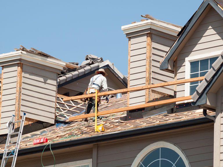 roofing contractors demolishing an asphalt roof in Triad NC