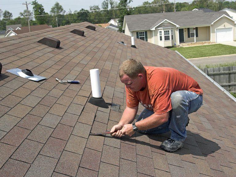 a man using a chisel on an asphalt roof
