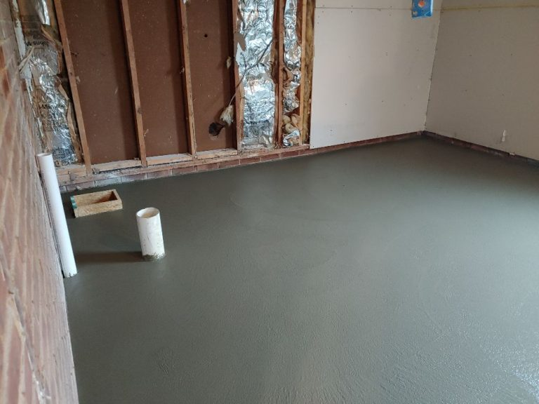 a room currently under renovation with a newly cemented floor and tear down wall