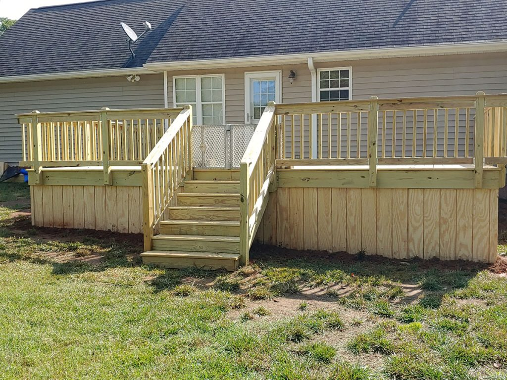 A front pace of a house with a wood deck and stairs and a grass