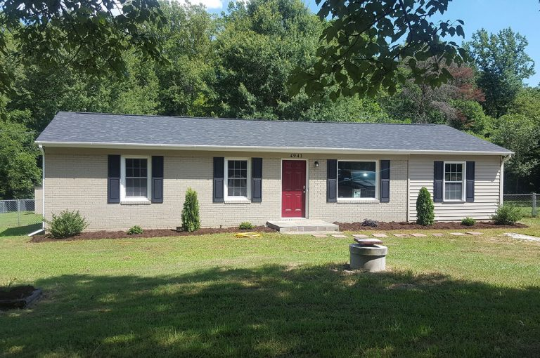 a house with an asphalt roofing in front of the forest located in Triad NC