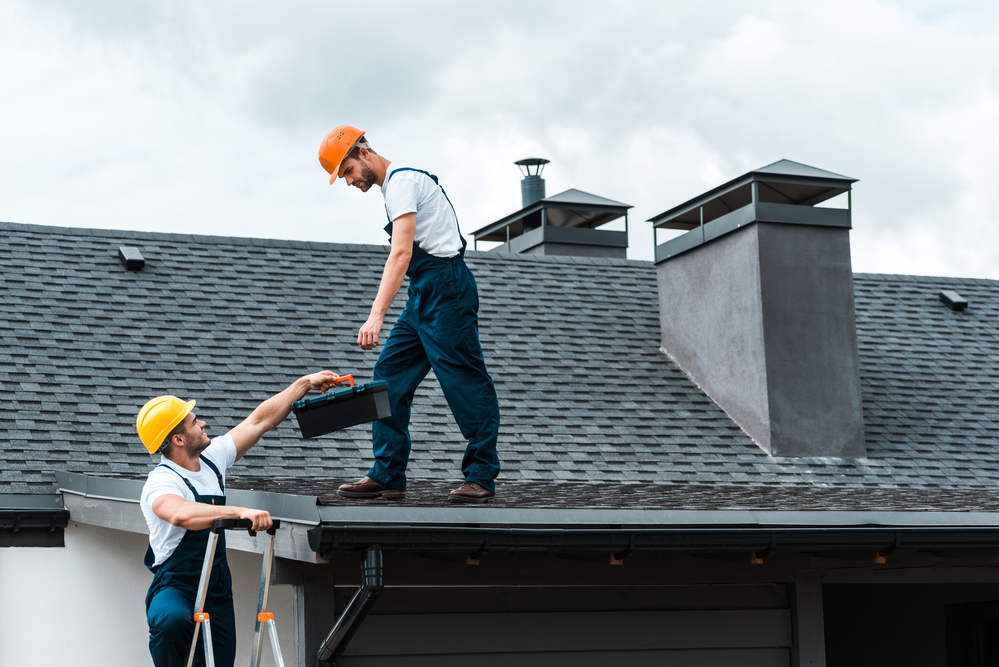 Home remodelers remodeling a house roof